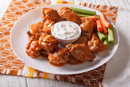 hot wings: buffalo wings with cheese sauce and celery on the table close-up. horizontal