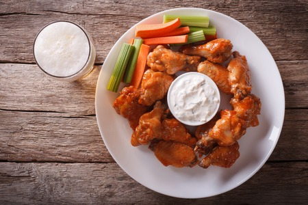 baked chicken: American fast food: buffalo wings with sauce and beer on the table. horizontal view from above