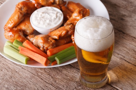 hot wings: buffalo hot wings with white sauce and beer on the table close-up horizontal