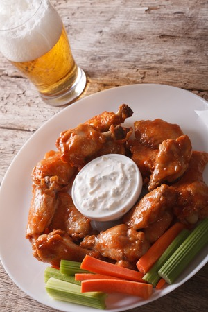 hot wings: buffalo hot wings with white sauce and beer on the table close-up vertical