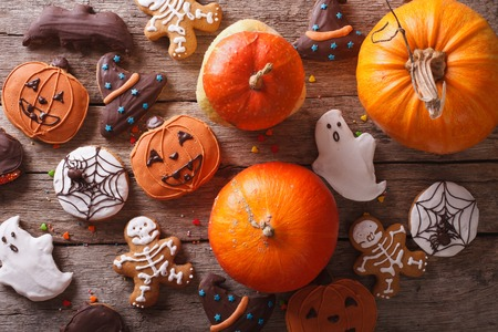 Beautiful gingerbread for Halloween and fresh pumpkin on the table. horizontal view from above Фото со стока