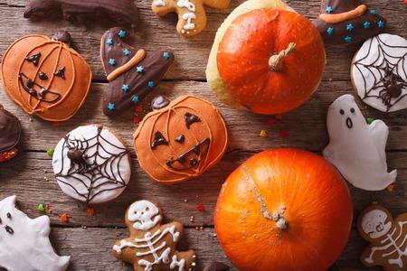 Schöne Lebkuchen für Halloween und frischen Kürbis close-up auf den Tisch. horizontale Ansicht von oben