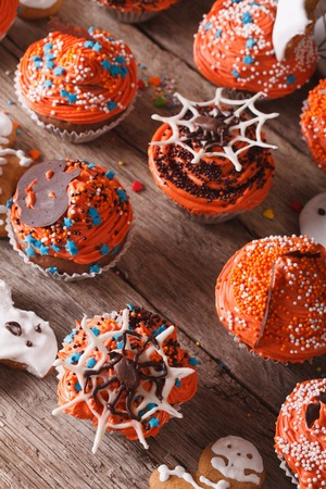 wood spider: Beautiful orange cupcakes Halloween close-up on the table. vertical top view Stock Photo