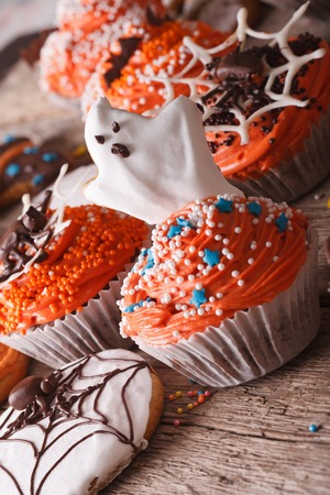 Halloween orange cupcakes with ghosts close-up on the table. vertical