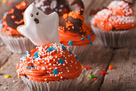 Delicious Halloween cupcakes with a spooky on a table close-up. horizontal