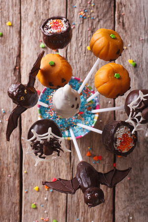 fondant fancy: Festive Halloween pop cakes on a table close-up. vertical top view