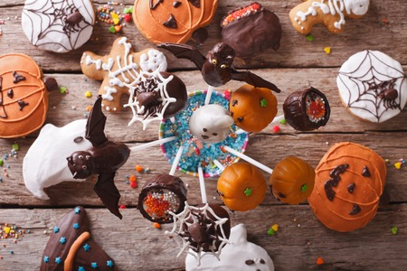 eating cake: Halloween Pop cakes and gingerbread cookies on the table. horizontal view from above Stock Photo