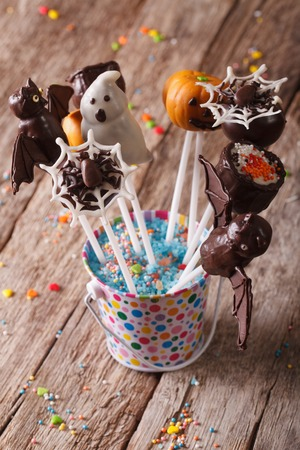 fondant fancy: Halloween cake pop decorated with icing in a bucket on the table. vertical