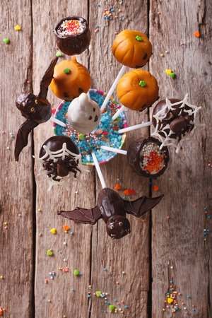 fondant fancy: Festive Halloween pop cakes on a table. vertical top view Stock Photo