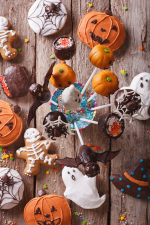 fondant fancy: Halloween Pop cakes and gingerbread cookies on the table. vertical top view