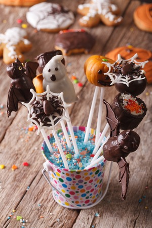fondant fancy: Beautiful delicious cake pop Halloween in a bucket on the table. vertical