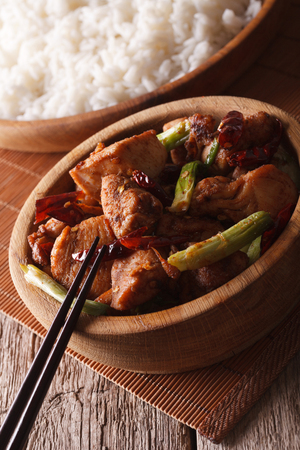 pao: Kung pao chicken in a bowl close up and rice on the table