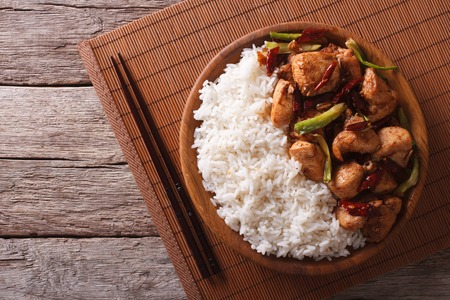 food dish: Rice with spicy kung pao chicken on a plate. horizontal view from above