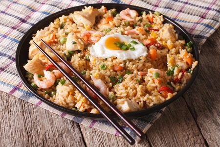 Asian fried rice with chicken, prawns, egg and vegetables close-up horizontal