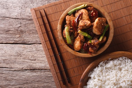 pao: Kung pao chicken fillets in a bowl and rice. horizontal view from above