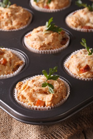 appetizer muffins with ham and cheese in baking dish close up on the table Stock Photo