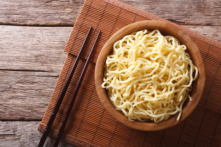 Asian ramen noodles in wooden bowl on the table. horizontal view from above