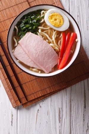 japanese cooking: Asian Food: Ramen noodles in broth with pork, vegetables and egg in a bowl close up. vertical top view Stock Photo