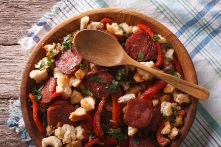 andalusian cuisine: Spanish migas with chorizo, bread crumbs and vegetables close-up on a plate. horizontal top view