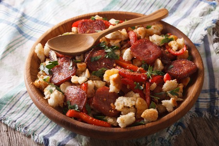 spanish: Spanish migas with chorizo, bread crumbs and vegetables close-up on a plate