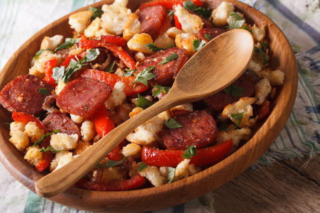 andalusian cuisine: Spanish migas with chorizo, bread crumbs and vegetables close-up on a plate. horizontal