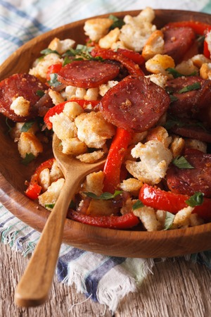 andalusian cuisine: Spanish rustic migas with chorizo and vegetables close-up on a plate Stock Photo