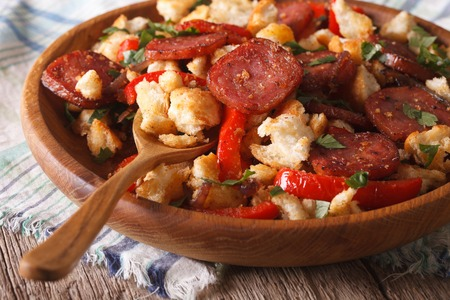 andalusian cuisine: Homemade Spanish migas with chorizo and vegetables close-up on a plate