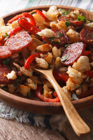 andalusian cuisine: Spanish migas with chorizo and vegetables close-up on a plate Stock Photo