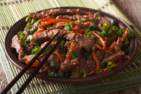 Asian cuisine: slices of beef fried with sesame and carrot close-up on a plate