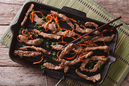 meat food: Korean bulgogi beef with carrot and onion on grill pan. horizontal view from above