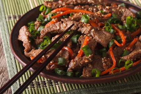 korea food: Asian food: slices of beef fried with sesame seeds and carrots closeup