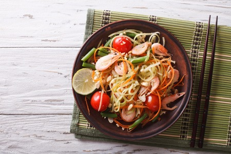 Thai green papaya salad with shrimp on a plate on the table. horizontal view from above