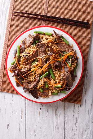 lo mein: Chinese noodles with beef, muer and vegetables close-up on a plate. vertical top view