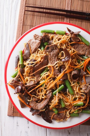 lo mein: Lo mein with beef, muer and vegetables close-up on a plate. vertical top view