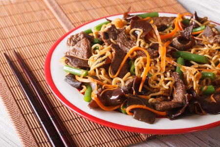 lo mein: Lo mein with beef, muer and vegetables close-up on a plate. horizontal Stock Photo