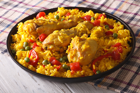 Spanish paella with chicken and vegetables close up on a plate. horizontal
