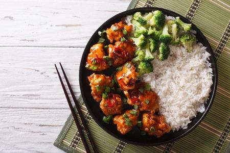 chinesisch essen: Tso Huhn mit Reis, Zwiebeln und Brokkoli auf dem Tisch. horizontale Ansicht von oben
