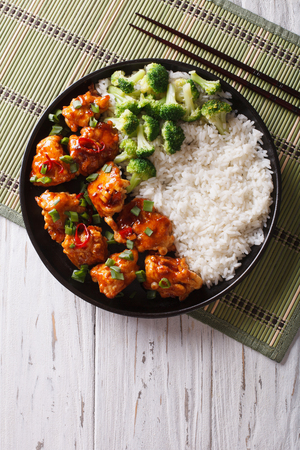 human meat: General Tsos chicken with rice, onions and broccoli on the table. vertical top view Stock Photo