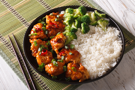 General Tsos chicken with rice, onions and broccoli close-up on a plate. horizontal