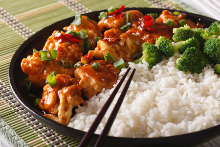 Asian Chicken tso with rice and broccoli close-up on a plate. Horizontal