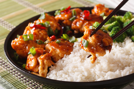 Asian food: General Tsos chicken with rice for dinner. Horizontal close-up