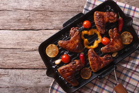 pepe nero: Ali di pollo alla griglia con verdure in una padella griglia primo piano. vista orizzontale dall'alto