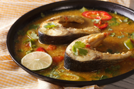 kerala culture: Delicious spicy fish curry with vegetables close-up on a plate