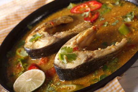 indian food: Spicy fish curry with vegetables close-up on a plate Stock Photo