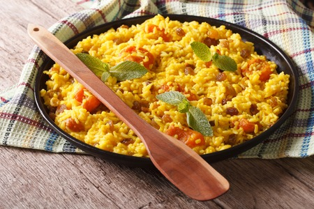 rustic food: Delicious sweet rice with saffron and dried fruits close-up on the table Stock Photo