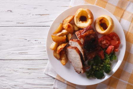 pub: Sunday Roast: pork with potatoes, vegetables and Yorkshire pudding close up on the table. horizontal view from above