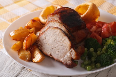 baked pork with potatoes, fresh vegetables and Yorkshire pudding on the plate closeup Stockfoto