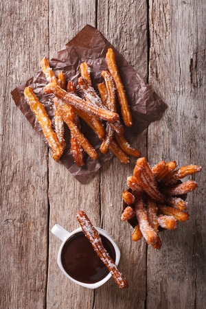 churros: churros and hot chocolate on the table. vertical top view Stock Photo