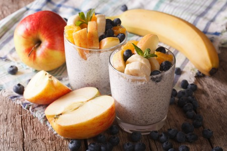 Healthy breakfast: fruit, yogurt, and chia seeds in a glass close-up on the table.