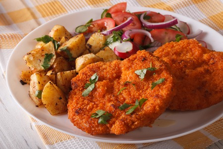 wiener: Wiener schnitzel, fried potatoes and vegetable salad on the plate closeup. Stock Photo
